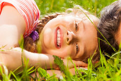 Close up view of happy girl laying on green grass Stock Photos