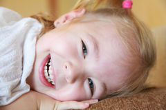 Close up view of a happy little girl with blue eyes laying down Royalty Free Stock Image