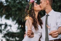 Close-up view of happy wedding couple holding sparklers and kissing. Selective focus stock photo