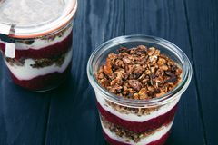 Close up view on healthy Homemade Granola Parfait in jar with jam. stock photo