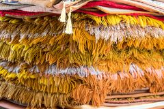 A close-up view of a heap of decorative carpet. With fringes. Pile of carpet for prayer and meditation on the floor of Buddhist temple Royalty Free Stock Image