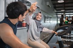 Close up view high five at the gym doing cardio exercises. On static bike royalty free stock photos