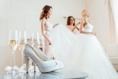 High heels and champagne with bride with bridesmaids. Close-up view of high heels and champagne with bride and bridesmaids blurred on background royalty free stock photography