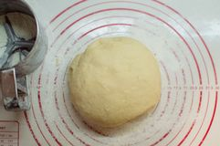 Close-up view of the homemade raw wheat dough ball lying on the modern cooking surface. Dough for pizza, pasta, potstickers. royalty free stock photo
