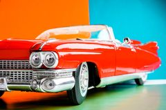 Close up view of the hood and headlights. Antique US red car. Scale model on colorful background stock photography