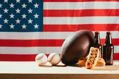 Close-up view of hot dogs, beer bottles and balls on wooden table with us flag. Behind stock images