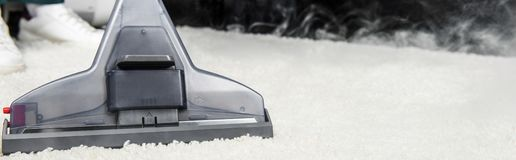 close-up view of hot steam cleaning of white carpet with professional vacuum royalty free stock image