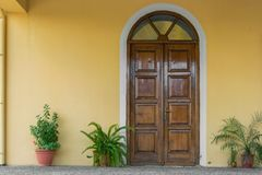 Close up view of house facade , close wooden door and potted plants. Close up view of house facade - close wooden door and potted plants stock photo