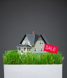 Close up view of house model with grass and sale tablet Stock Image