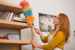 Close up view of housewife cleaning dust with colorful brush. Royalty Free Stock Image
