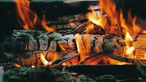 Close up view of a huge burning firewood or logs lie on the green and burn in the flames of fire in open air stock video