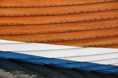 Close up view of the hull of a fishing boat. Close up view of the hull of a clinker built fishing boat with varnished and painted planks of white and blue royalty free stock photography