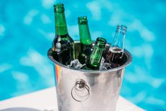 Close-up view of Ice bucket with beer standing next to swimming pool Stock Photography