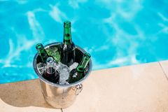 Close-up view of Ice bucket with beer standing next to swimming pool Stock Images