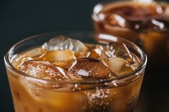 Close up view of ice cubes in cold brewed coffee in glass on dark background royalty free stock photos