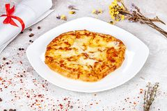 Close-up view on Imeretian Imeruli khachapuri on the plate. royalty free stock image