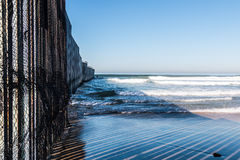 Close-Up View of International Border Wall in San Diego. Close-up view of the international border wall extending out into the ocean between San Diego royalty free stock images
