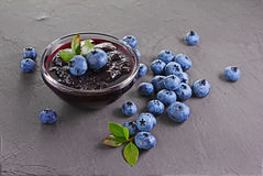 Close up view jam in glass bowl with fresh ripe blueberry and leaves. On black background royalty free stock photography