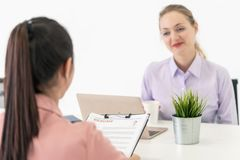 Close up of job interview focusing on woman handing resume with the office stock photography