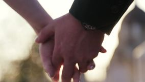 A close up view of joining just married wife and husband hands, holding hands. Happy moments. No people around. Outside. Shooting, hands on bright sunlight stock video