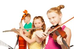 Close-up view of kids playing musical instruments. Close-up view of kids playing on musical instruments together on white background Royalty Free Stock Photography