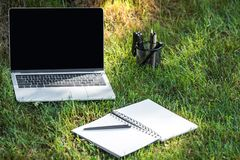 Close up view of laptop with blank screen and empty textbook with pen on grass. Outdoors stock photo