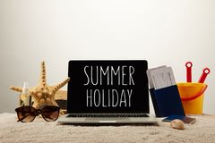 Close up view of laptop with summer holiday lettering, sea star, sunglasses, passports with tickets and toy bucket on sand on grey. Background Stock Photo
