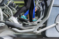 Close up view on legs of people exercising on the crosstrainer m. Achines in fitness center Royalty Free Stock Images