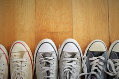 Close-up view of a line of several pairs of vintage sneakers on a wood floor. Royalty Free Stock Images
