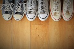 Close up view of a line of several pairs of vintage sneakers on a wood floor. Stock Image