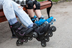 Close-up view at the in-line skates wearing on mother and children legs, people sitting on bench Royalty Free Stock Image