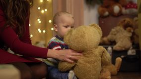 Close up view of little cute child playing with big teddy bear at home. Mother sitting near the son holding shaking toy. And helping her baby. Concept of stock video