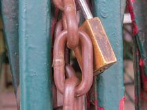 Close up view of lock and chain closing gate. Close up view of rusty lock and chain closing old and worn gate Royalty Free Stock Image