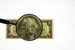 Close up view of magnifying glass over two dollar bill. Banknote. Beautiful backgrounds royalty free stock photo