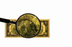 Close up view of magnifying glass over two dollar bill. Banknote. Beautiful backgrounds stock photography