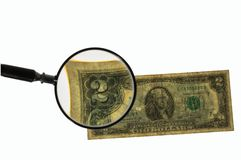 Close up view of magnifying glass over two dollar bill. Banknote. Beautiful backgrounds royalty free stock images
