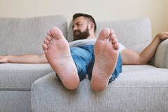 Close up view of male bare feet on sofa. Close up view of male bare feet. Bearded adult tired sleeping hipster guy on beige sofa, selective focus Stock Images