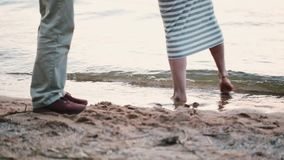 Close-up view of male and female feet standing on the shore of the sea. Young couple spending time on the beach. stock video