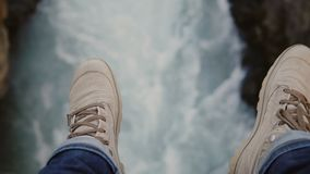 Close-up view of male foot over the turbulent stream of water flowing through the rocks, mountains river. Traveling man enjoying the beautiful landscape of stock footage