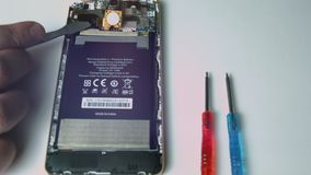 Close up view of male hand holding used Phone battery to repair and replace battery Phone.