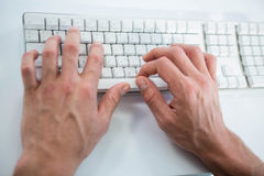 Close up view of a male hand typing on keyboard. On white background Stock Photos