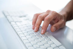Close up view of a male hand typing on keyboard. On white background Royalty Free Stock Photo