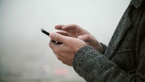 Close-up view of male hands holding the mobile phone with touchscreen. Young man using smartphone in foggy park. stock footage