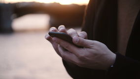 Close-up view of male hands holding the smartphone and typing on touchscreen, standing on embankment on sunset. stock video