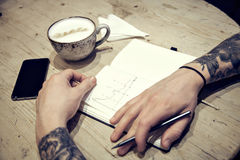 Close-up view of male hands with note book and coffee top view. On wood table Stock Photo
