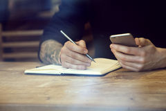 Close-up view of male hands with notebook and phone cafe indoor. Behind window Stock Image