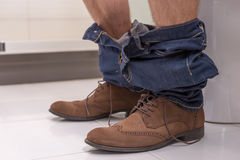 Close up view of male sitting on the toilet seat. Close up view of male wearing jeans and shoes sitting on the toilet seat in the modern tiled bathroom at home Royalty Free Stock Photos