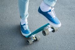 Penny skateboard commute hipster transport solutions. Close-up view of the man in blue jeans and canvas scateshoes standing on the blue penny board and ready for Royalty Free Stock Photos