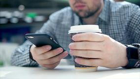 Close up view of man in cafe uses his smartphone and holds cup of coffee. stock video footage