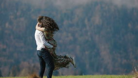 The close-up view of the man carrying round the girl in the long rustic dress in the mountains. stock footage
